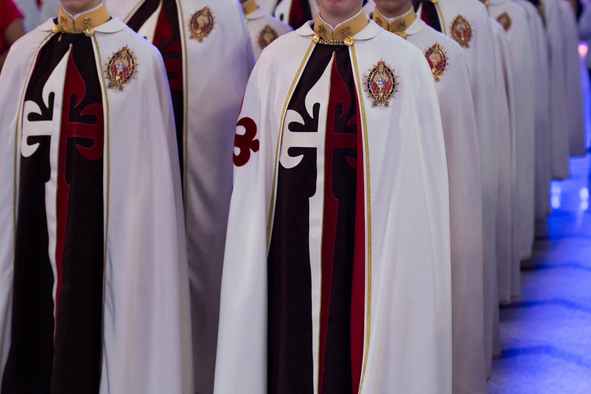 A grande cruz do escapulário, com pontas estilizadas que lembram flores-de-lis, é inspirada na Cruz de Santiago de Compostela
