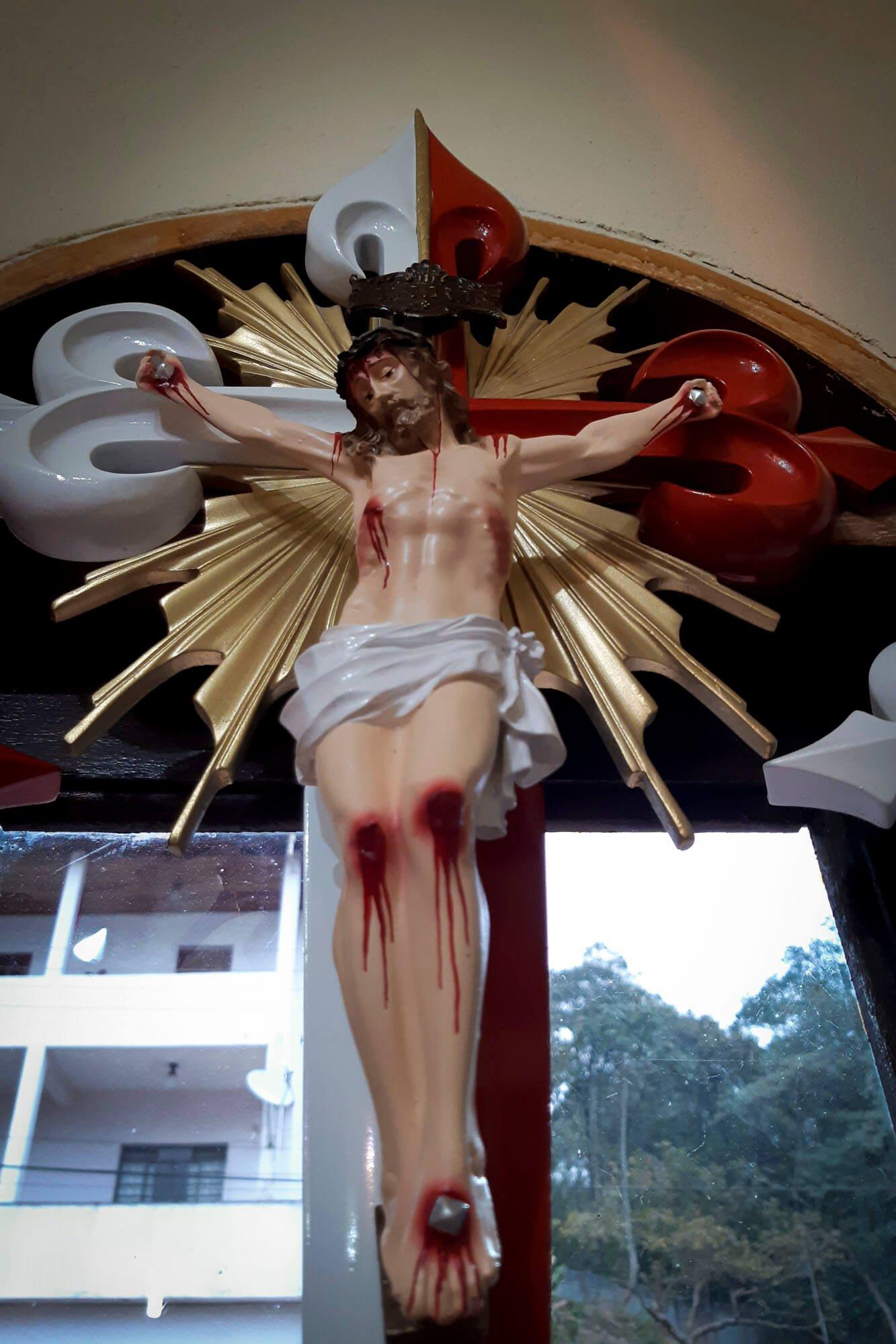 A grande cruz com pontas estilizadas aparece por toda parte, até nas imagens de Jesus