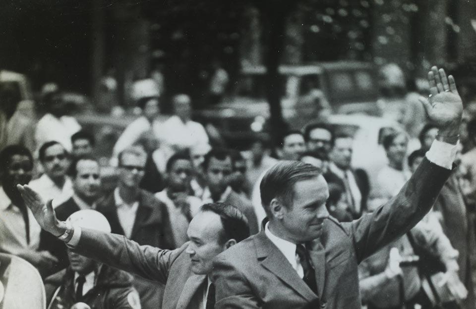 Michael Collins e Neil Armstrong acenam durante passeio de carro aberto
