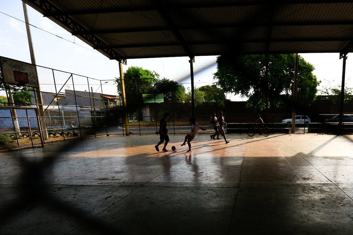 Na frente do local do crime bárbaro, meninos jogam futebol em uma quadra esportiva