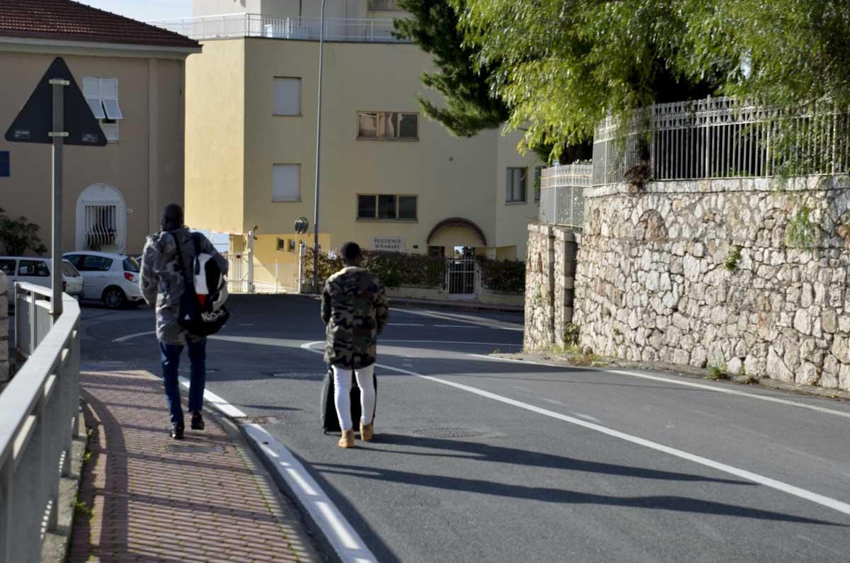 Migrantes caminham pelas rodovias de Grimaldi, a última vila italiana antes da fronteira